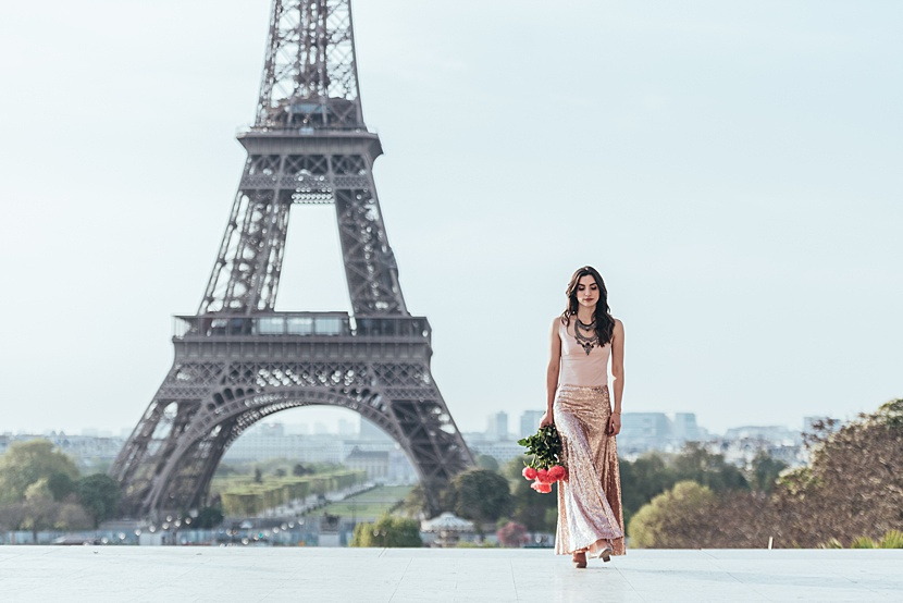Paris portrait of a woman walking in front of the Eiffel Tower during her boudoir photography session with gloria villa